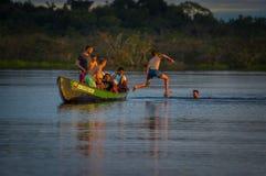 CUYABENO,厄瓜多尔- 2016年11月16日:跳进盐水湖的年轻游人重创反对日落, Cuyabeno 免版税图库摄影