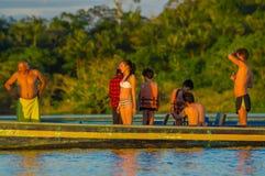 CUYABENO,厄瓜多尔- 2016年11月16日:跳进盐水湖的年轻游人重创反对日落, Cuyabeno 库存照片