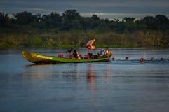 CUYABENO,厄瓜多尔- 2016年11月16日:跳进盐水湖的年轻游人重创反对日落, Cuyabeno 库存图片