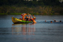 CUYABENO, ΙΣΗΜΕΡΙΝΟΣ - 16 ΝΟΕΜΒΡΊΟΥ 2016: Νέοι τουρίστες που πηδούν στη λιμνοθάλασσα Grande ενάντια στο ηλιοβασίλεμα, Cuyabeno Στοκ Εικόνα
