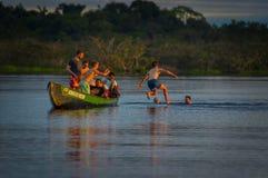 CUYABENO, ΙΣΗΜΕΡΙΝΟΣ - 16 ΝΟΕΜΒΡΊΟΥ 2016: Νέοι τουρίστες που πηδούν στη λιμνοθάλασσα Grande ενάντια στο ηλιοβασίλεμα, Cuyabeno Στοκ Φωτογραφίες