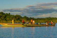 CUYABENO, ЭКВАДОР - 16-ОЕ НОЯБРЯ 2016: Молодые туристы готовые для того чтобы поскакать в лагуну большую против захода солнца, Cu Стоковое Изображение