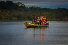 CUYABENO, ЭКВАДОР - 16-ОЕ НОЯБРЯ 2016: Молодые туристы скача в лагуну большую против захода солнца, Cuyabeno Стоковая Фотография