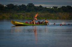 CUYABENO, ЭКВАДОР - 16-ОЕ НОЯБРЯ 2016: Молодые туристы скача в лагуну большую против захода солнца, Cuyabeno Стоковое Изображение