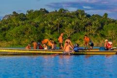 CUYABENO, ЭКВАДОР - 16-ОЕ НОЯБРЯ 2016: Молодые туристы скача в лагуну большую против захода солнца, Cuyabeno Стоковая Фотография RF