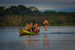 CUYABENO, ЭКВАДОР - 16-ОЕ НОЯБРЯ 2016: Молодые туристы скача в лагуну большую против захода солнца, Cuyabeno Стоковые Фотографии RF