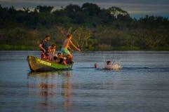 CUYABENO, ЭКВАДОР - 16-ОЕ НОЯБРЯ 2016: Молодые туристы скача в лагуну большую против захода солнца, Cuyabeno Стоковые Фото