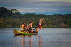 CUYABENO, ЭКВАДОР - 16-ОЕ НОЯБРЯ 2016: Молодые туристы скача в лагуну большую против захода солнца, Cuyabeno Стоковое Фото