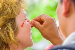 CUYABENO, ECUADOR 6 DE MAYO DE 2017: Pintura turística no identificada su cara usando las semillas del achiote de estas vainas ro Foto de archivo
