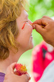CUYABENO, ECUADOR- MAY 06, 2017: Unidentified tourist painting her face using achiote seeds from these spiny red pods Stock Photo
