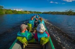CUYABENO, ECUADOR - NOVEMBER 16, 2016: Niet geïdentificeerde mensen die door boot in de diepte van de Wildernis van Amazonië binn Stock Afbeelding