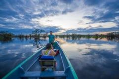 CUYABENO ECUADOR - NOVEMBER 16, 2016: Oidentifierat folk som tycker om solnedgången från floden i den Cuyabeno nationalparken Arkivbild