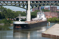 On the Cuyahoga River. A Great Lakes self discharging bulk carrier navigates a tight bend in the Cuyahoga River at Cleveland, Ohio. Ships like this transport stock images