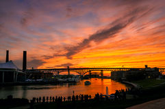 Cuyahoga solstice. A silhouetted crowd of phototgraphers lines the east bank of the Cuyahoga River in Cleveland to shoot the summer solstice sunset Royalty Free Stock Image