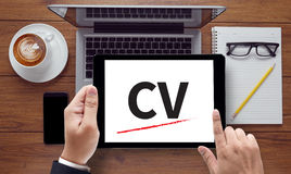 CV - Curriculum Vitae. On the tablet pc screen held by businessman hands - online, top view Royalty Free Stock Photo