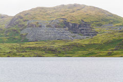 Cwmystradllyn Slate Quarry on hillside, lake in foreground. Stock Images