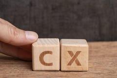 CX, концепция опыта клиента, блок куба удерживания руки деревянный аранжировать слово с алфавитом CX с темной предпосылкой, важно стоковые фото