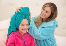 CXlose oben der jungen Mutter, die zu ihrer kleinen Tochter ein blaues Tuch im Kopf aplying ist, während beide das Tragen Bademän lizenzfreie stockfotos
