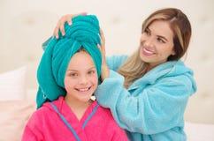 CXlose oben der jungen Mutter, die zu ihrer kleinen Tochter ein blaues Tuch im Kopf aplying ist, während beide das Tragen Bademän lizenzfreies stockbild