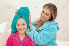 CXlose oben der jungen Mutter, die zu ihrer kleinen Tochter ein blaues Tuch im Kopf aplying ist, während beide das Tragen Bademän stockbilder