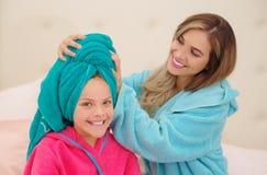 CXlose oben der jungen Mutter, die zu ihrer kleinen Tochter ein blaues Tuch im Kopf aplying ist, während beide das Tragen Bademän lizenzfreies stockfoto