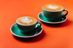Cyan coffee cups over orange background. stock photos