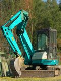 Cyan excavator. New cyan excavator in the parking lot Royalty Free Stock Image