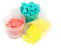 Cyan, magenta and yellow crushed chalk. In plastic caps on white Royalty Free Stock Image