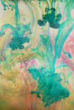 Cyan and pink swirled ink. Design of cyan, pink and yellow colored inks in liquid royalty free stock photography