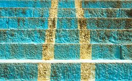 Receding cyan colored stairs, with dual white stripes running through the center. These cyan steps have grown old, and their color is being lost. White stripes stock photography