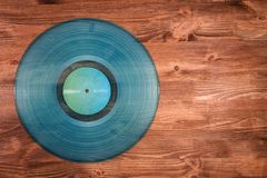 Cyan vinyl record on brown wooden background Royalty Free Stock Photography