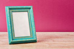 Cyan vintage photo frame. Cyan vintage photo frame on old table with pink wall Stock Photo