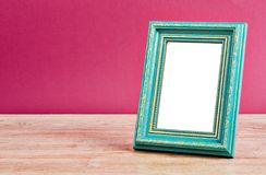 Cyan vintage photo frame. Cyan vintage photo frame on old table with pink wall, Save clipping path Stock Image