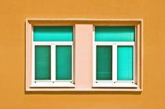 Cyan windows on yellow wall Stock Photo