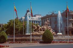 Cybele fountain with Spanish flags and old buildings in Madrid. Charming Cybele fountain with Spanish flags and old buildings on the busy Alcala Street in Madrid royalty free stock photo