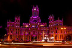 Cybele Palace at night in Madrid. Cybele Palace at the Plaza de Cibeles with light trails of the traffic at night, Madrid, Spain. Purple and red illumination Royalty Free Stock Image