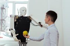 Joyful nice boy talking to the robot royalty free stock image