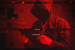 Cyber attack with unrecognizable hooded hacker using tablet comp