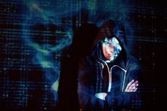 Cyber attack with unrecognizable hooded hacker using virtual reality, digital glitch effect Stock Images