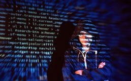Cyber attack with unrecognizable hooded hacker using virtual reality, digital glitch effect Stock Photo