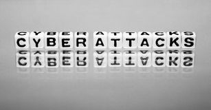 Cyber attacks. Words on the white reflective background stock photo