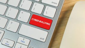 Cyber bullying red button on silver keyboard. The cyber bullying red button on silver keyboard royalty free stock image