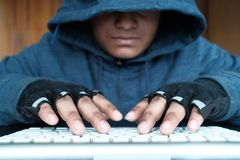 Cyber crime and computer virus concept with hooded person working on laptop Royalty Free Stock Photos
