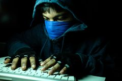 Cyber crime and computer virus concept with hooded person working on laptop. Cyber crime and computer virus concept with hooded faceless person working on laptop Royalty Free Stock Photos
