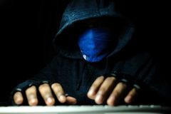 Cyber crime and computer virus concept with hooded person working on laptop. Cyber crime and computer virus concept with hooded faceless person working on laptop Royalty Free Stock Photo