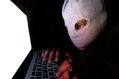 Cyber crime and computer virus concept with hooded faceless person working on laptop.  Royalty Free Stock Photo