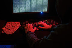 Cyber crime in internet. The man in the hood checks the malicious code on the keyboard. Cybercrime through the Internet Stock Photos