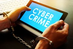 Cyber crime. Man in handcuffs holding tablet with sign Cyber crime Royalty Free Stock Image