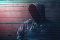Cyber crime and network security concept. Unrecognizable faceless man wearing hooded jacket with digital glitch effect stock photo