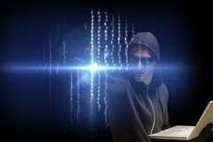 Cyber criminal is holding a laptop against matrix code rain background. Digital composite of hacker stock image